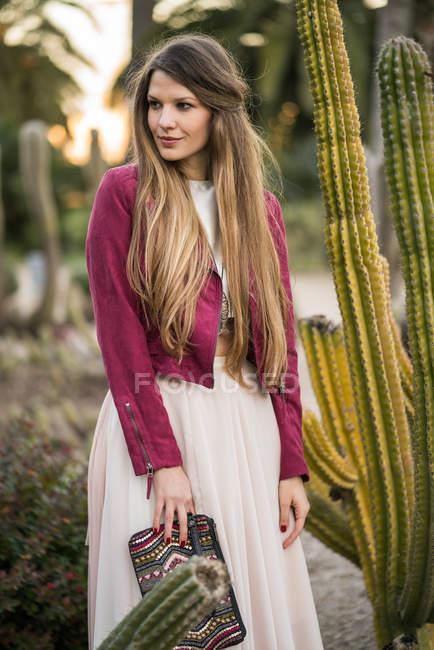 Donna sorridente vicino a cactus — Foto stock