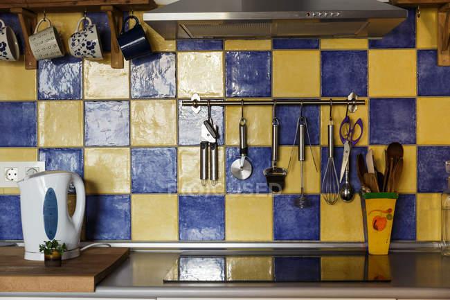La superficie de trabajo con estufa eléctrica y cubiertos en la cocina - foto de stock