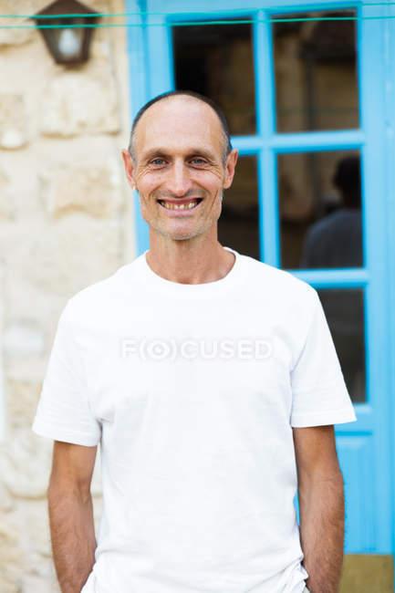 Retrato de homem sorridente em camisa branca olhando para a câmera — Fotografia de Stock