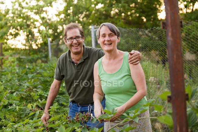 Пара старших взрослых, смеется в саду — стоковое фото