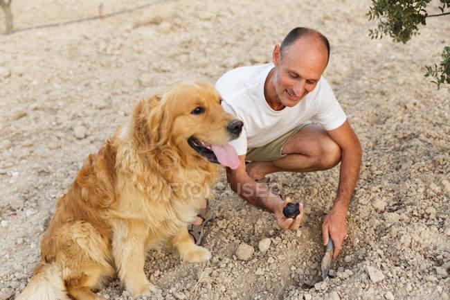 Männer mit Golden-Retriever-Hund und Schaufel in der Hand graben ein Loch — Stockfoto