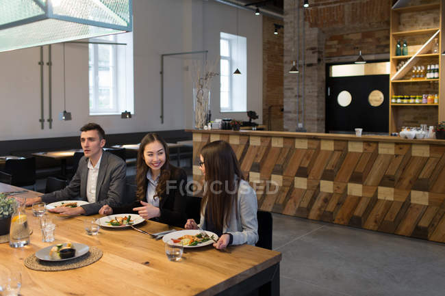 Group of colleagues sitting at cafe and talking — Stock Photo