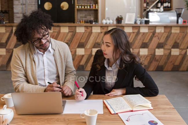Dois colegas de trabalho, sentado com laptop e trabalhar juntos em documento — Fotografia de Stock