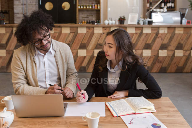 Two coworkers sitting with laptop and working on document together. — Stock Photo