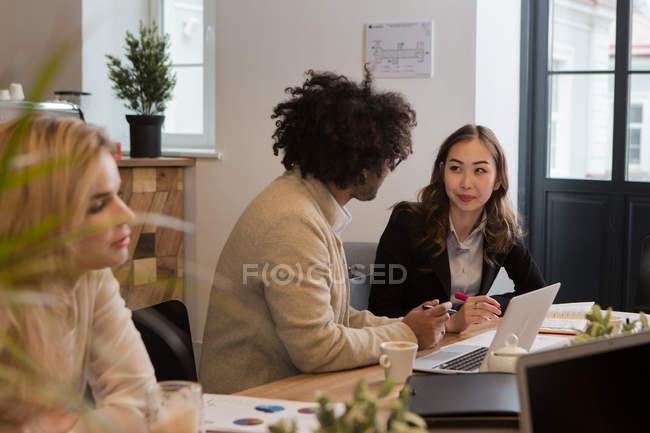 Colaboradores sentados com laptop e trabalhando em documento juntos . — Fotografia de Stock