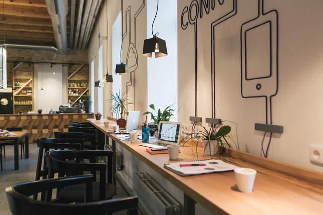 Interior da cafetaria com laptop e documentos na mesa — Fotografia de Stock