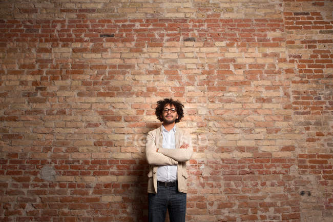 Man in casual clothing and glasses posing with hands crossed on background of brick wall. — Stock Photo