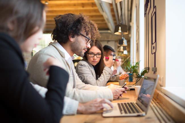 Vista lateral de jovens trabalhadores de escritório sentados na área de trabalho e trabalhando com laptop no escritório moderno . — Fotografia de Stock