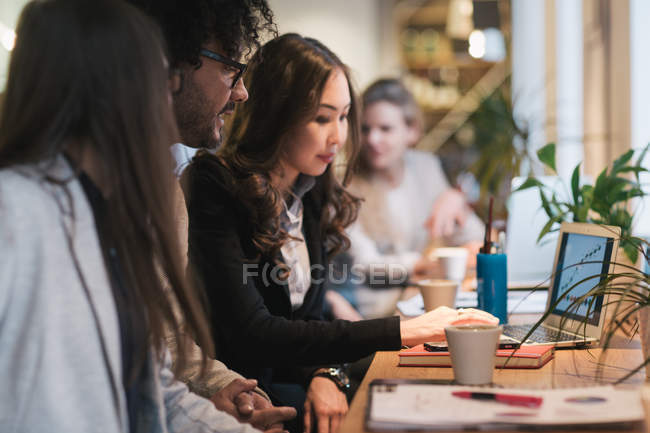 Side view of young office workers sitting at desktop with laptop in modern office. — Stock Photo