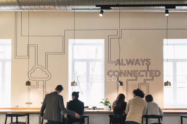 Visão traseira de pessoas sentadas na área de trabalho perto da janela e conversando no escritório leve . — Fotografia de Stock