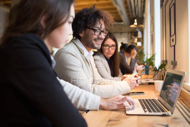 Коллеги сидят за рабочим столом и наблюдают за ноутбуком во время обсуждения в современном офисе . — стоковое фото