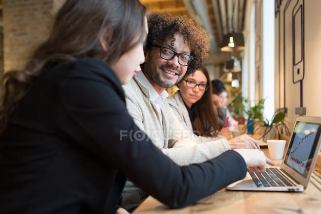 Cheerful coworkers sitting at desktop and watching laptop — Stock Photo