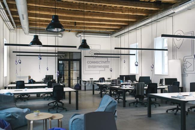 Plan intérieur de bureau spacieux et lumineux meublé avec des bureaux, des chaises et décoré avec un plafond en bois . — Photo de stock