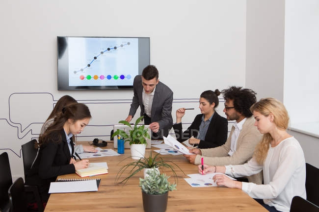 Group of young people sitting at table and working with diagrams in  office. — Stock Photo