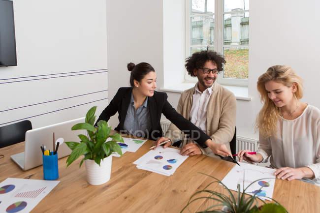 Три сотрудника сидят за столом и работают над диаграммами в офисе — стоковое фото