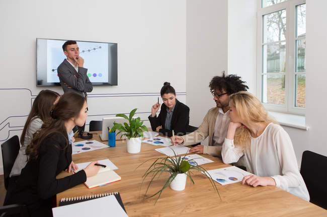 Group of young colleagues working with diagrams while meeting — Stock Photo