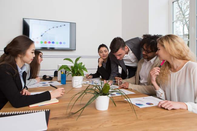 Groupe de jeunes collègues discuter des schémas tout en répondant — Photo de stock