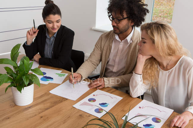 Three colleagues working on diagrams at table in office — Stock Photo
