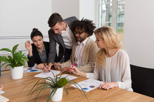 Колегами, обговорювати діаграм разом у світло-офіс. — стокове фото