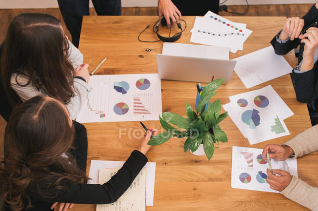 From above view of table with colleagues discussing diagrams — Stock Photo