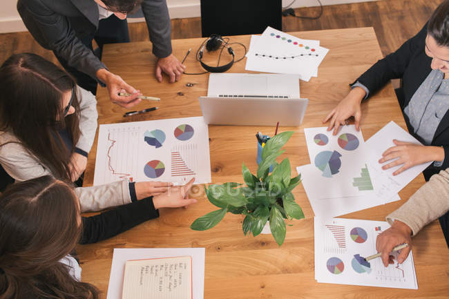 From above view of team of workers sitting at table and working with diagrams. — Stock Photo