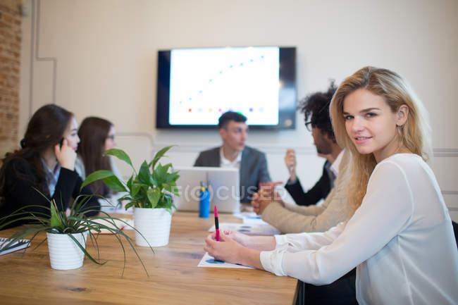 Молодая блондинка сидит за столом с коллегами и смотрит в камеру в офисе . — стоковое фото