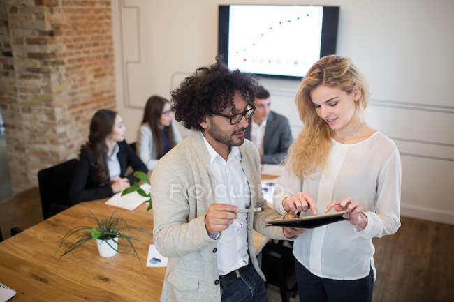 Двое его коллег с цифровой вкладку говорить в современном офисе — стоковое фото