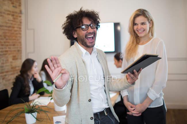 Веселый человек с планшетом смеется над камерой в офисе — стоковое фото