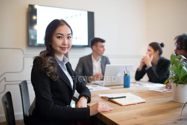 Young woman sitting at desktop with co-workers and looking at camera in office. — Stock Photo