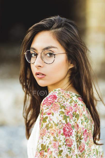 Девушка в очки, глядя через плечо — стоковое фото