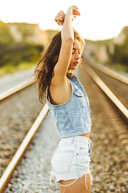 Garota em jeans posando ao longo da estrada de ferro — Fotografia de Stock