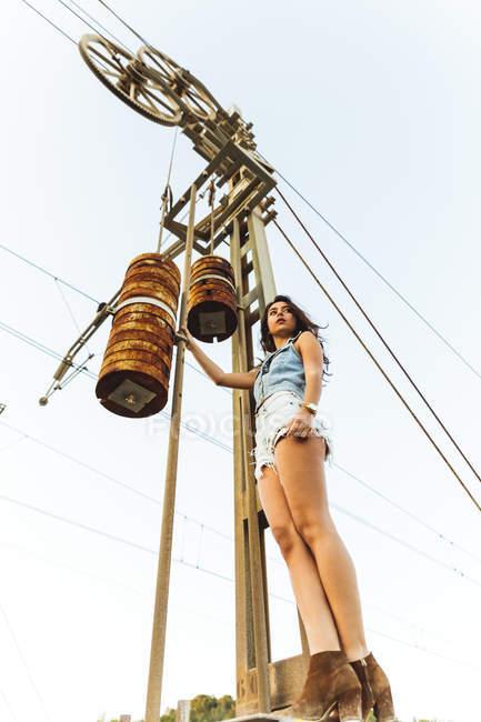 Jeune fille debout au pylône industrielle — Photo de stock