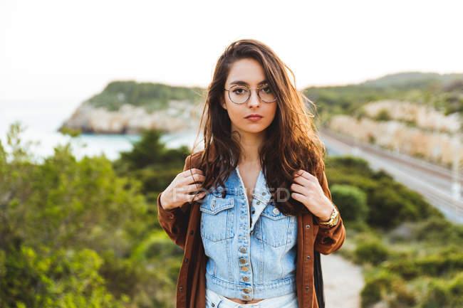 Girl adjusting backpack and looking at camera — Stock Photo