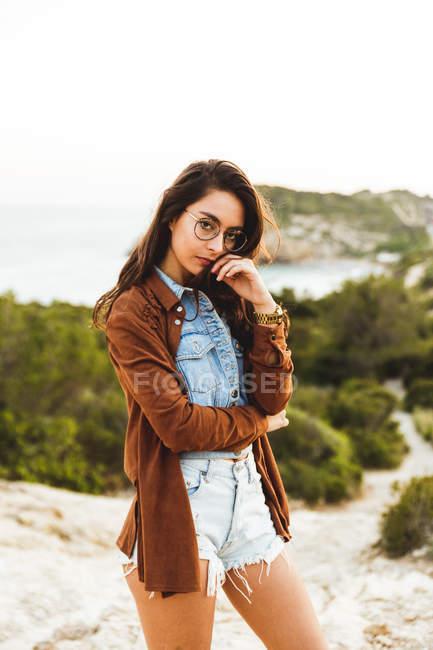 Girl in eyeglasses posing over nature landcape — Stock Photo