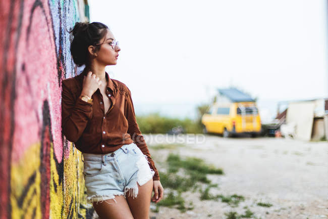 Girl with leaning on graffiti wall — Stock Photo