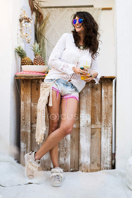 Молода жінка, маючи прохолодними напоями — стокове фото