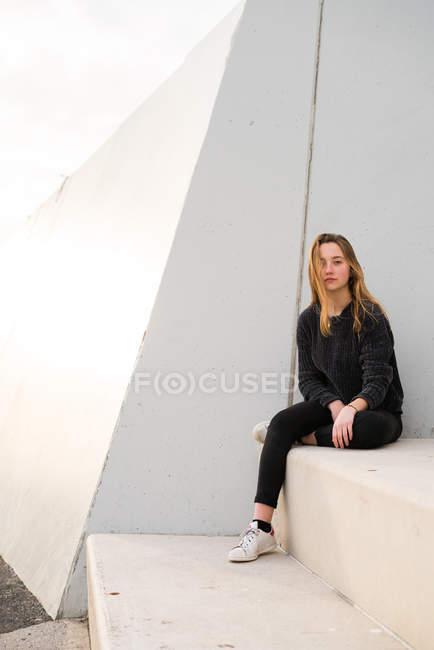 Chica joven en escaleras de hormigón - foto de stock