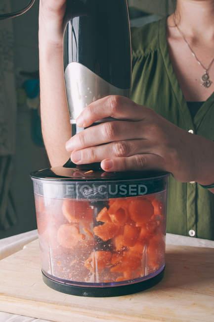 Mujer de las manos para picar zanahoria fresca en la cocina más - foto de stock