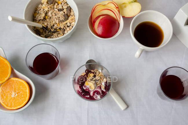 Vista plana de yogur con mermelada y granola con tazas de café y frutas - foto de stock