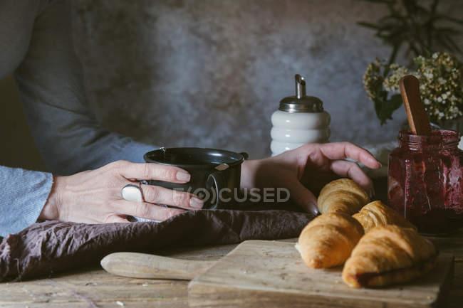 Femmes mains tenant coupe et croissant de prise — Photo de stock