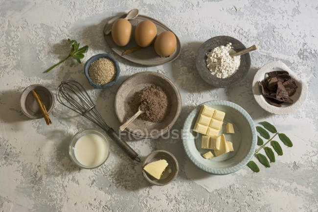 Delicious baking ingredients in bowls on stone table — Stock Photo