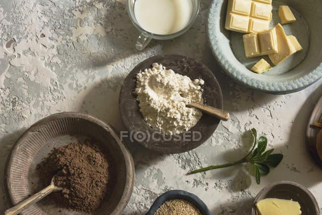 Directamente sobre la vista de cuencos con los ingredientes dispuestos en la mesa de piedra - foto de stock