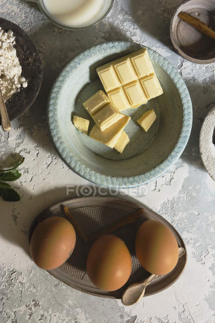 Directly above view of bowls with eggs and white chocolate bars — Stock Photo