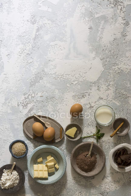 Bowls with baking ingredients on stone table — Stock Photo