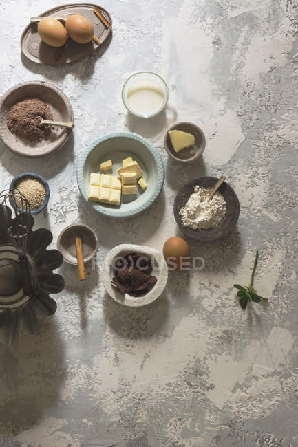 Arrangement of bowls with baking ingredients on stone table — Stock Photo