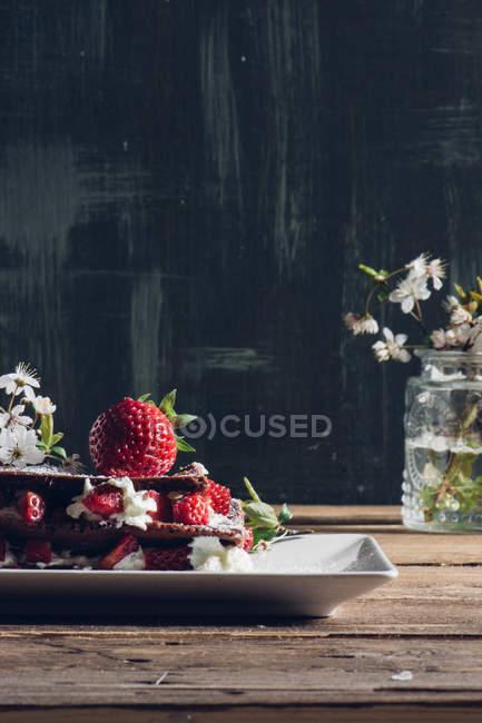 Stillleben mit hausgemachtem Erdbeer Torte und blühende Zweige auf Holztisch — Stockfoto