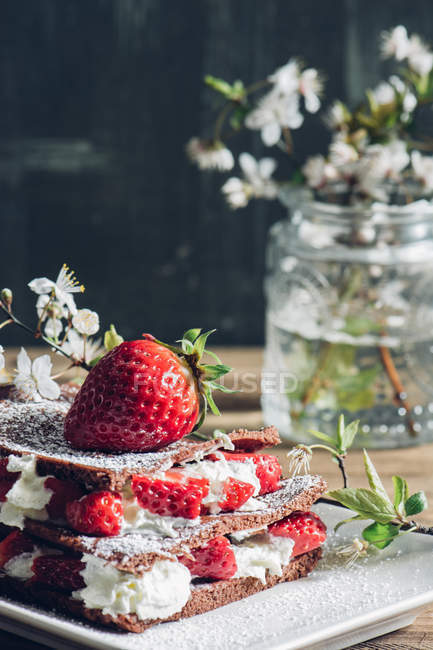 Still life of homemade strawberry tart and blooming twigs — Stock Photo