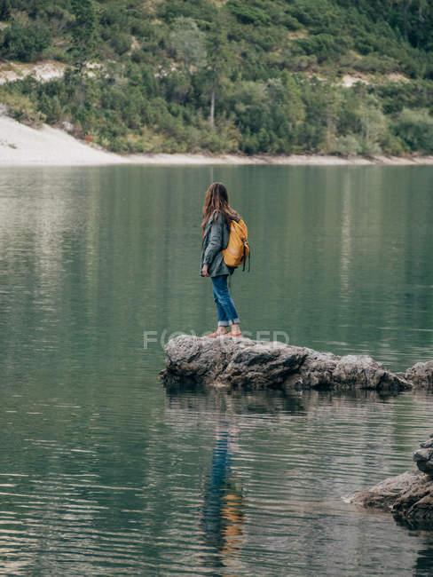 Female backpacker on stone in lake — Stock Photo