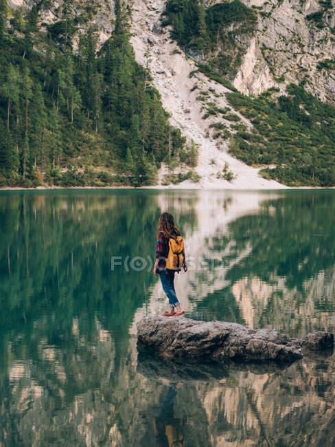 Frau mit Rucksack auf Stein im See — Stockfoto