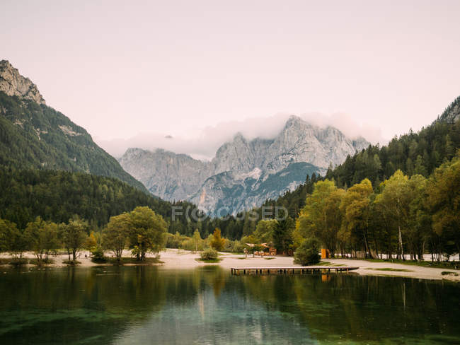 Lake with trees on banks and mountains — Stock Photo